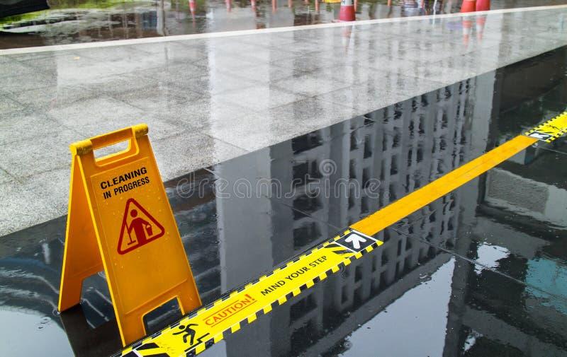 Het teken die waarschuwing van voorzichtigheids natte vloer tonen en let op de stap stock afbeeldingen