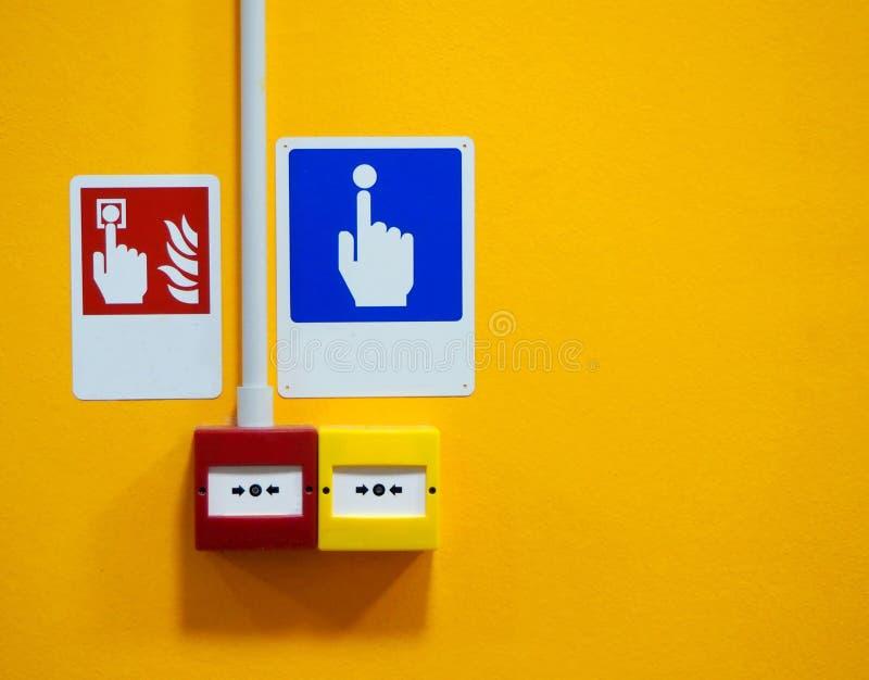 Het teken en het brandalarm van het noodoproeppunt roepen puntteken met de knopen op gele muurachtergrond te drukken stock fotografie