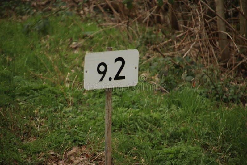 Het teken van de afstandskilometer in wit met zwarte langs spoor voor treinbestuurders stock fotografie