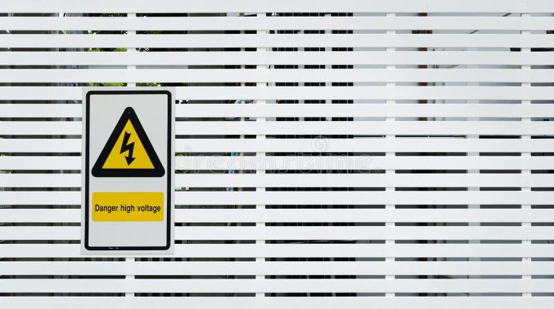 Het teken van de gevaarshoogspanning en achtergrondfoto royalty-vrije stock afbeelding