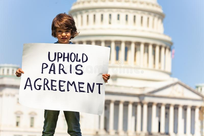 Het teken van de protesteerderholding bevestigt de overeenkomst van Parijs in handen royalty-vrije stock afbeelding