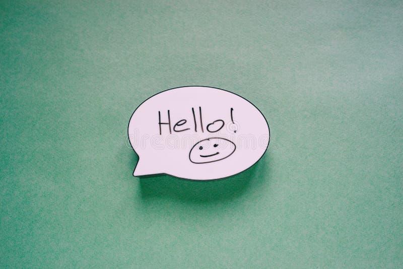 Het teken van de toespraakbel met de woorden Hello en Smiley Het symbool van het toespraakbericht op document groene achtergrond  royalty-vrije stock afbeelding
