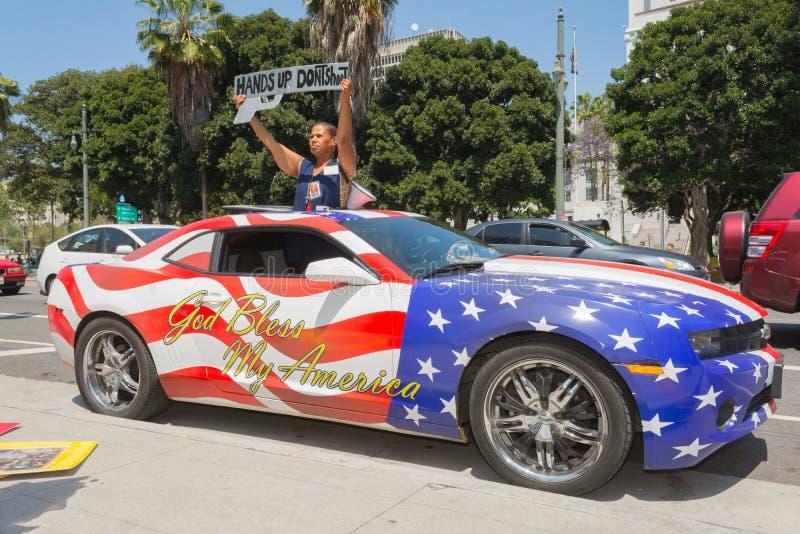 Het teken van de vrouwenholding naast een auto in Amerikaanse vlagkleuren die wordt geschilderd royalty-vrije stock fotografie