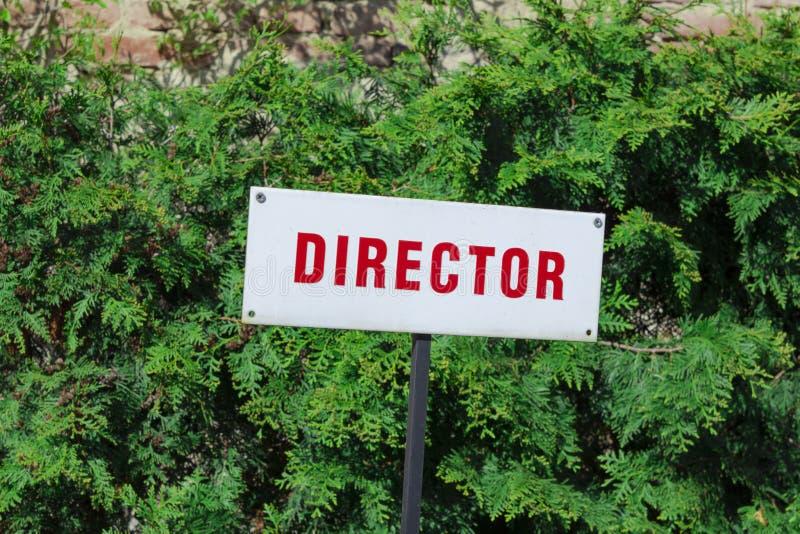 Het teken van het directeursparkeren, rode brieven, reserveerde plaats, achter groene natuurlijke achtergrond stock foto's