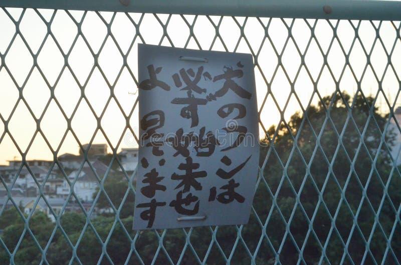 Het teken zegt de ACHTERSCHEPEN van UW HOND BEHANDEL, LET ik op U op de straat van Yokohama, Japan De straattekens betekent de ve royalty-vrije stock foto's