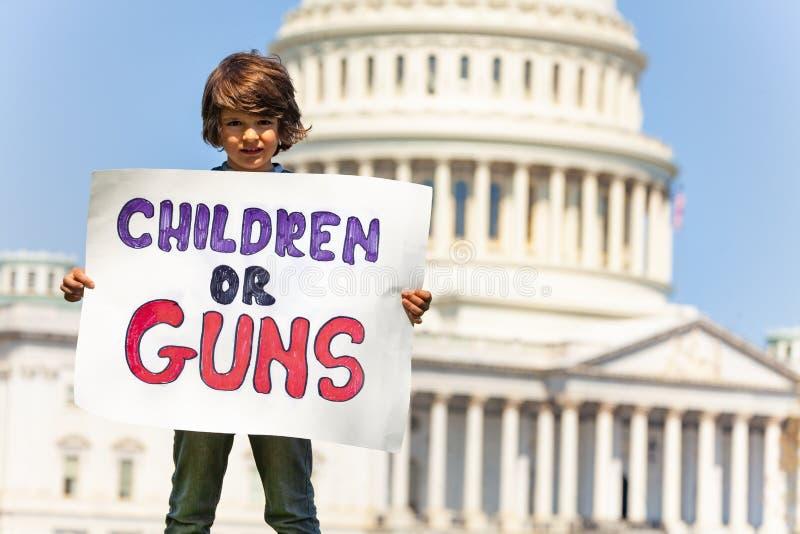 Het tekenkinderen of kanonnen van de protesteerderholding in handen stock fotografie