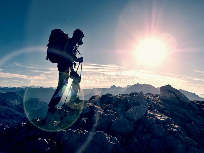 Het tekort van de lensgloed Toeristengids op trekkingsweg met polen en rugzak Ervaren wandelaar royalty-vrije stock afbeeldingen