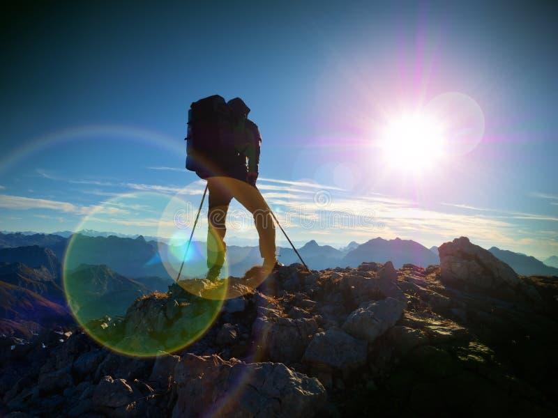 Het tekort van de lensgloed Toeristengids op trekkingsweg met polen en rugzak Ervaren wandelaar royalty-vrije stock afbeelding