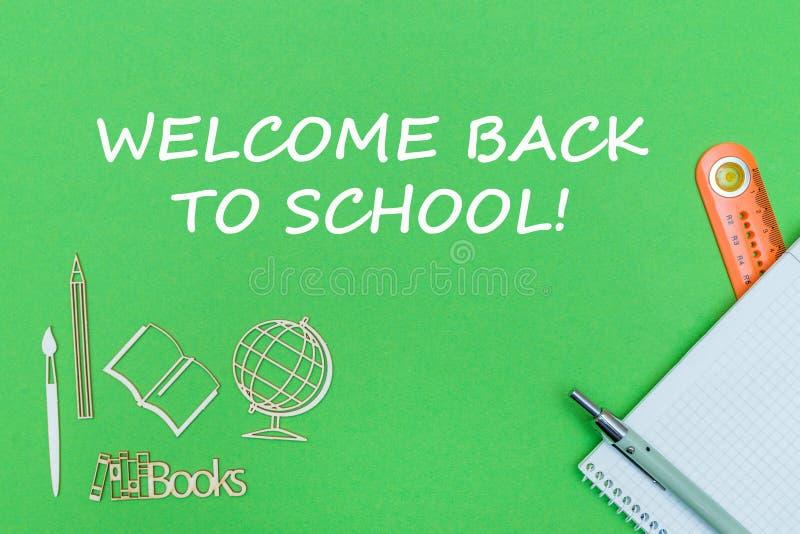 Het tekstonthaal terug naar school, school levert houten miniaturen, notitieboekje op groene achtergrond royalty-vrije stock fotografie