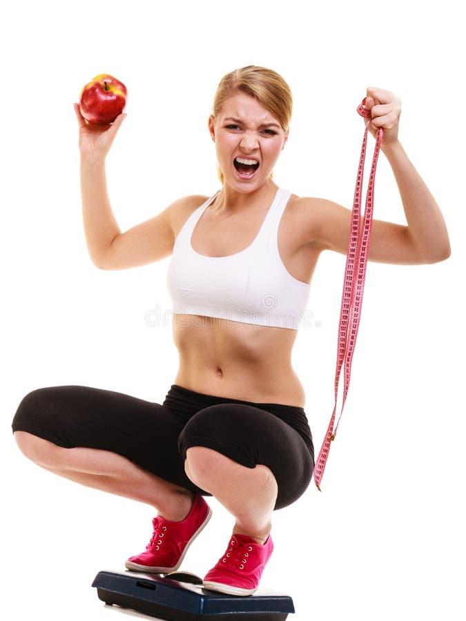 Het teleurgestelde vrouw wegen Het verlies van het dieetgewicht royalty-vrije stock afbeelding