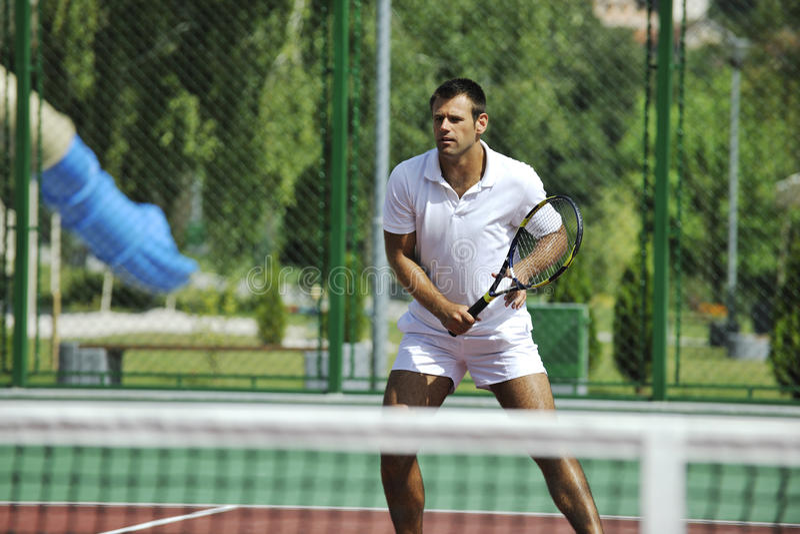 Het tennis van het jonge mensenspel openlucht stock afbeeldingen