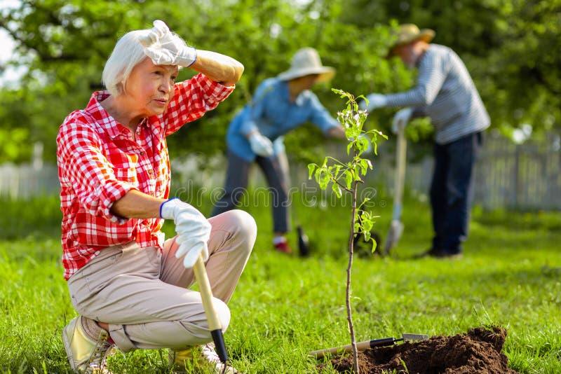 Het teruggetrokken vrouw dragen gloves gevoel dat na het werken in tuin wordt vermoeid royalty-vrije stock foto