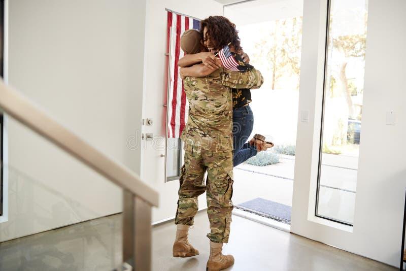 Het terugkeren van millennial Afrikaanse Amerikaanse militair die zijn vrouw opheffen van haar voeten in de deuropening van hun h royalty-vrije stock afbeeldingen