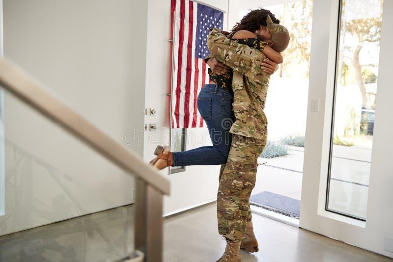 Het terugkeren van millennial Afrikaanse Amerikaanse militair die zijn vrouw opheffen van haar voeten in hun huis, zijaanzicht royalty-vrije stock foto