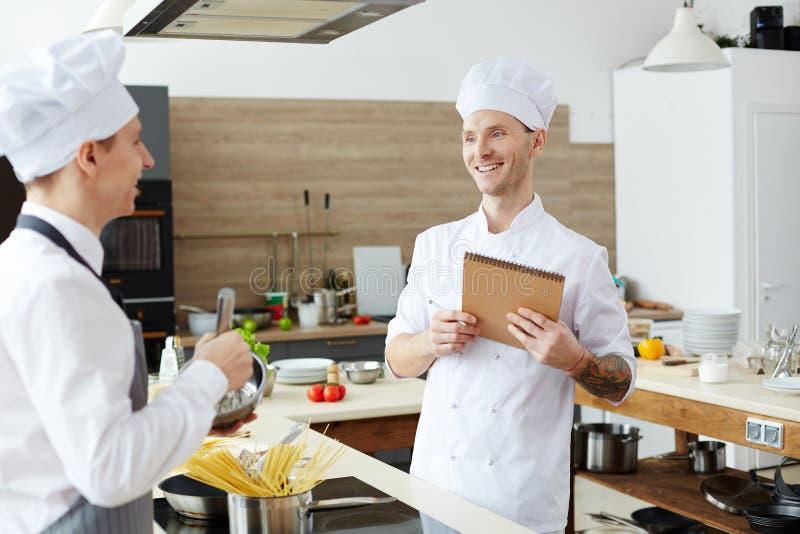Het tevreden chef-kok maken neemt van terwijl het testen van kok nota stock afbeeldingen