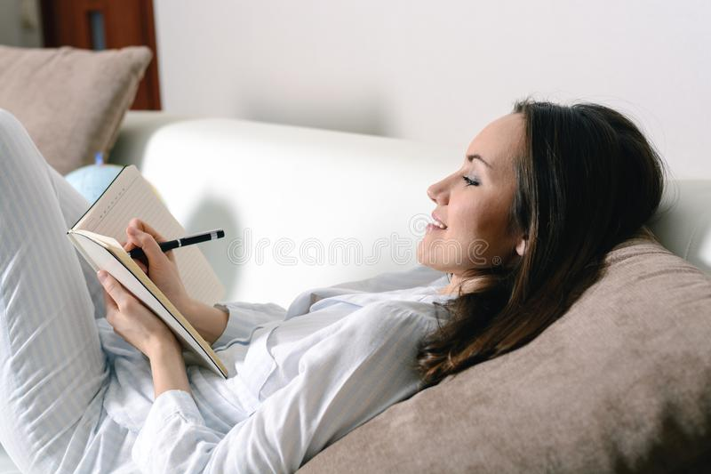 Het tevreden en gelukkige het glimlachen meisje liggen op de bank in de ruimte en schrijft een dagboek van uw dromen, plannen, do royalty-vrije stock afbeeldingen