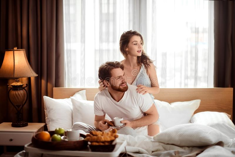 Het tevreden familiepaar heeft ontbijt in bed, geniet van heerlijke croissants, koffie en het fruit, ziet positief weg eruit, zit stock foto