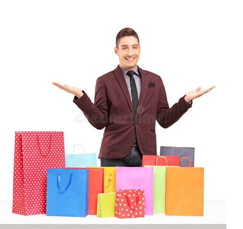 Het tevreden jonge mens stellen met overvloed van het winkelen zakken stock foto