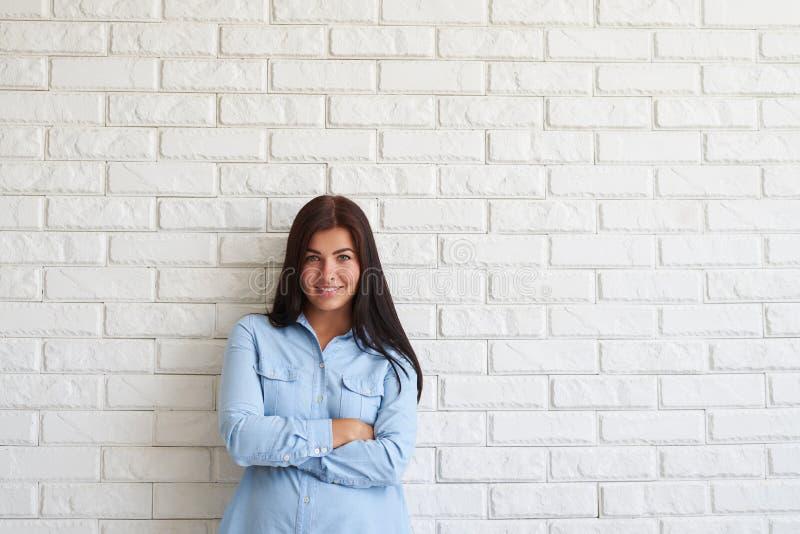 Het tevreden jonge vrouw houden bewapent gekruist en glimlachend terwijl tribune stock foto's