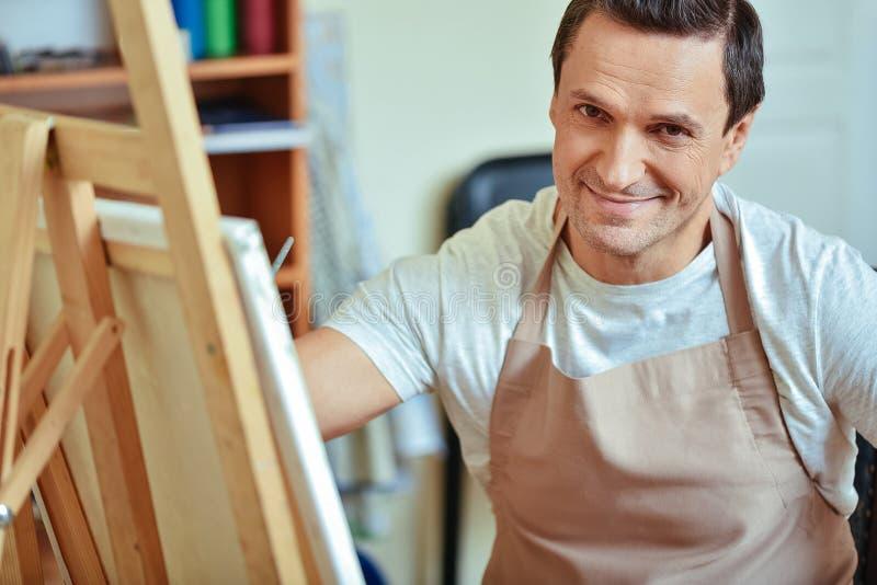 Het tevreden kunstenaar stellen in het schilderen van studio royalty-vrije stock afbeeldingen