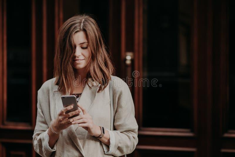 Het tevreden opgetogen vrouwelijke kereltje let op video op slimme telefoon, leest bankwezenbericht, gekleed in witte regenjas, s stock foto