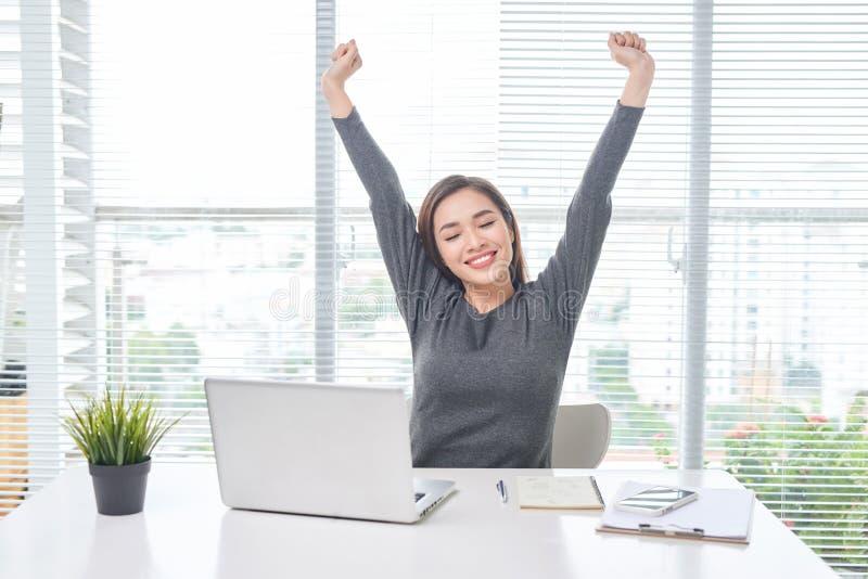 Het tevreden vrouw ontspannen met handen achter haar hoofd Gelukkige glimlachende werknemer na het afwerkingswerk, die goed nieuw royalty-vrije stock fotografie