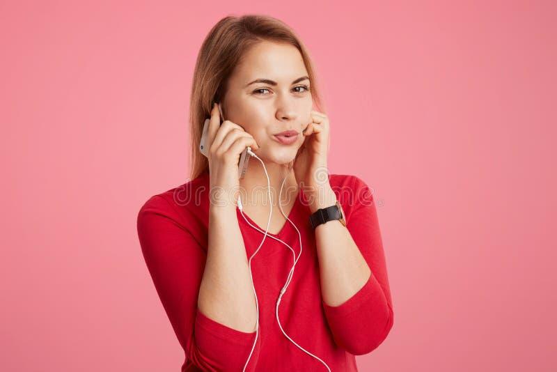 Het tevreden wijfje geniet van favoriet spoor in oortelefoons, gebruikt modern gadget, gelukkig om prettige muziek, over roze bac stock foto