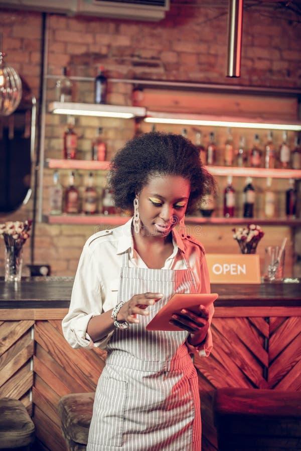 Het tevredenstellen van verleidelijke slanke jonge Afrikaans-Amerikaanse serveerster die informatie over tablet controleren royalty-vrije stock afbeeldingen
