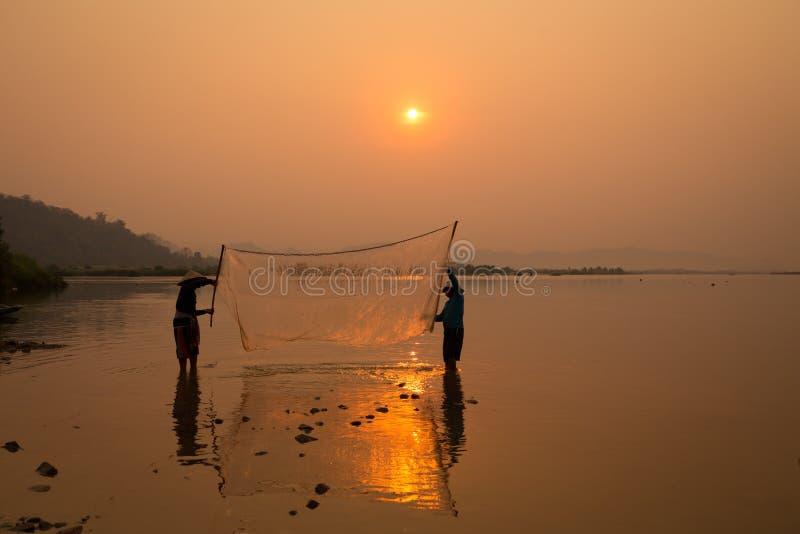 Het Thaise visserssilhouet in Mekong van het zonsopganglandschap rivier is royalty-vrije stock afbeelding