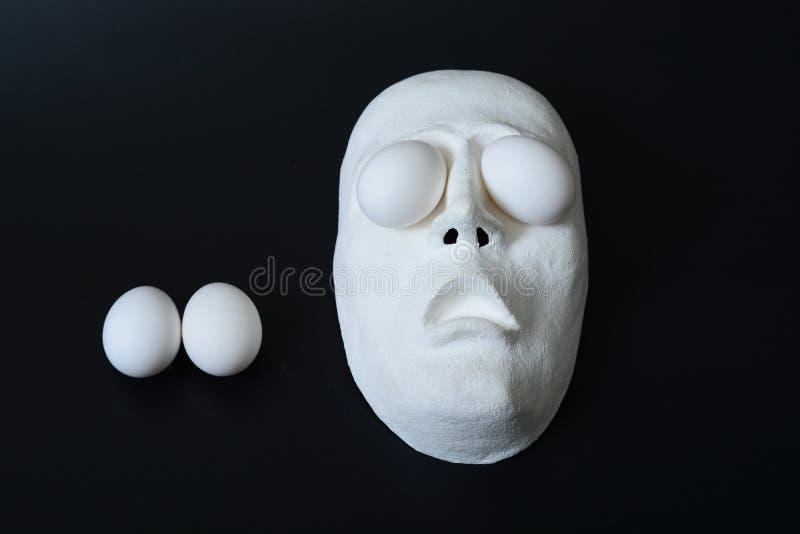 Het theatrale masker ligt in de eicontainer met kippeneieren royalty-vrije stock afbeeldingen