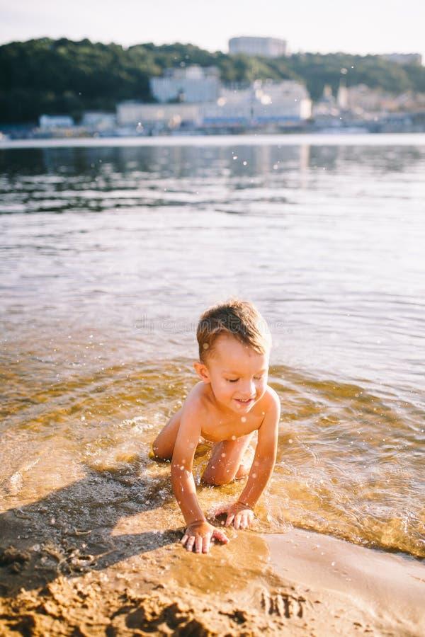 Het thema is de zomertijd en rust dichtbij het water Weinig blije Kaukasische grappige jongen speelt en geniet van in de rivier E stock afbeelding