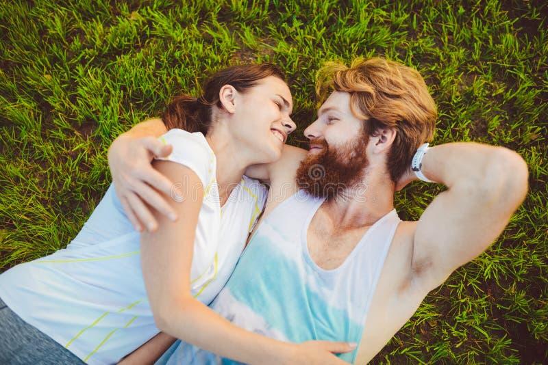 Het thema is sport en een gezonde levensstijl Een jonge man en vrouwenpaar rust het liggen op hun ruggen op het groene gras, een  stock foto