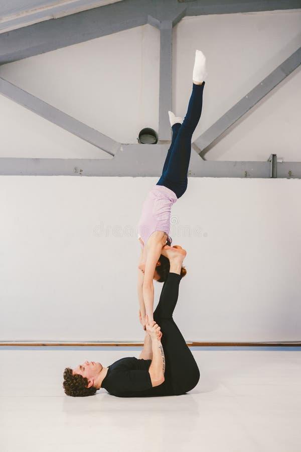Het thema is sporten en oppervlakte Een jong Kaukasisch mannetje en een wijfje koppelen het praktizeren acrobatische yoga in een  royalty-vrije stock fotografie