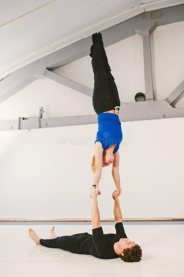 Het thema is sporten en oppervlakte Een jong Kaukasisch mannetje en een wijfje koppelen het praktizeren acrobatische yoga in een  royalty-vrije stock foto