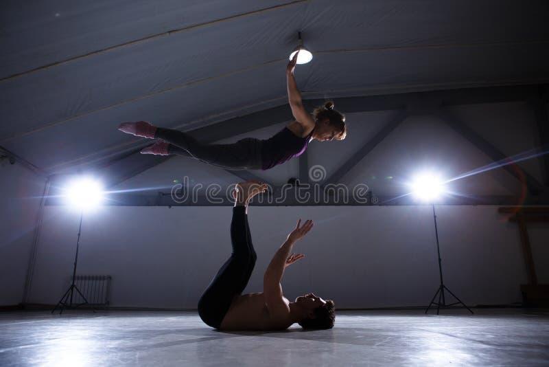 Het thema van Acroyoga en Yoga stelt Acroyogis het praktizeren met studio Backlight de Basisman werpt knalt vrouwenvlieger in fli stock afbeelding