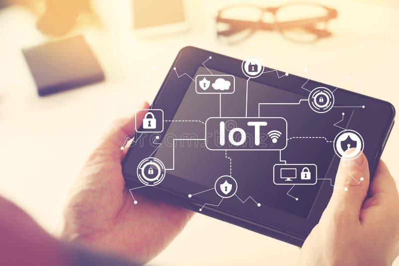 Het Thema van de IoTveiligheid met de tabletcomputer van de persoonsholding stock foto