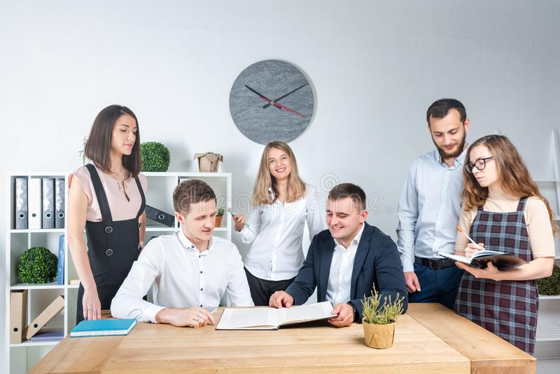 Het thema is zaken en groepswerk Een groep jonge Kaukasische mensenbeambten die een vergadering, briefing houden, die met documen stock afbeeldingen