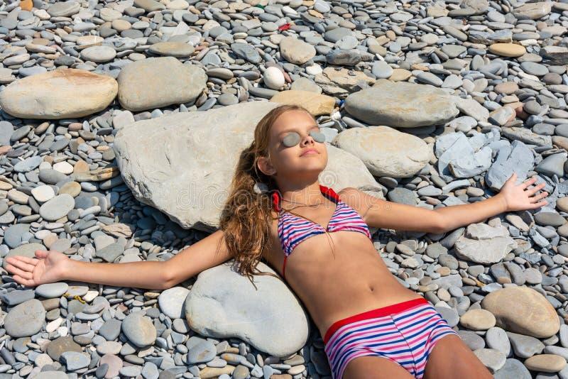 Het tien-jaar-oude meisje zonnebaadt op een rotsachtig strand, zettend kiezelstenen op haar ogen stock afbeelding