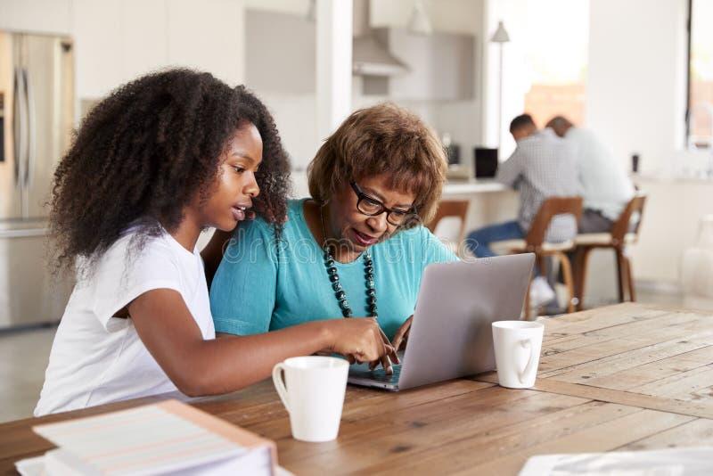 Het tiener Afrikaanse Amerikaanse meisje die haar grootmoeder helpen gebruikt een laptop computer thuis, omhoog sluit stock foto