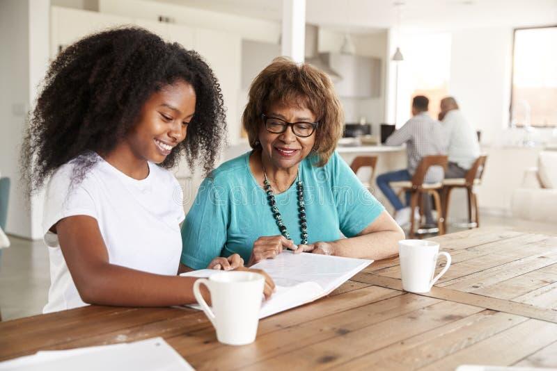 Het tiener Afrikaanse Amerikaanse meisje kijken door een fotoalbum met haar grootmoeder thuis, sluit omhoog stock fotografie