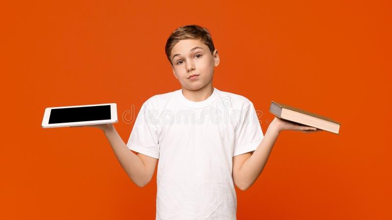 Het tienerjonge geitje kiest tussen Tablet en Boek royalty-vrije stock foto
