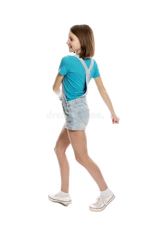 Het tienermeisje in denimoverall in het vliegen stelt, volledige hoogte Ge?soleerd op een witte achtergrond royalty-vrije stock afbeeldingen