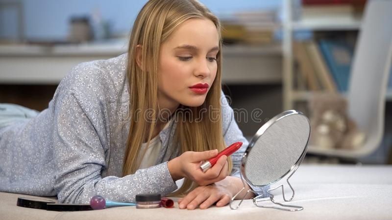 Het tienermeisje die met rode glanzende lippenstift op lippen in spiegel, het van toepassing zijn kijken maakt omhoog royalty-vrije stock foto's