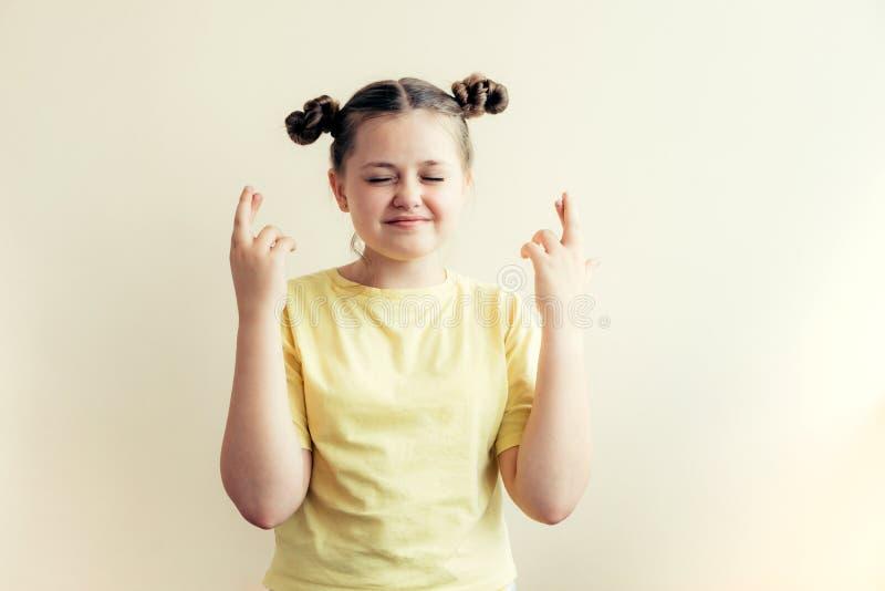 Het tienermeisje in een gele T-shirt kruiste haar vingers stock foto