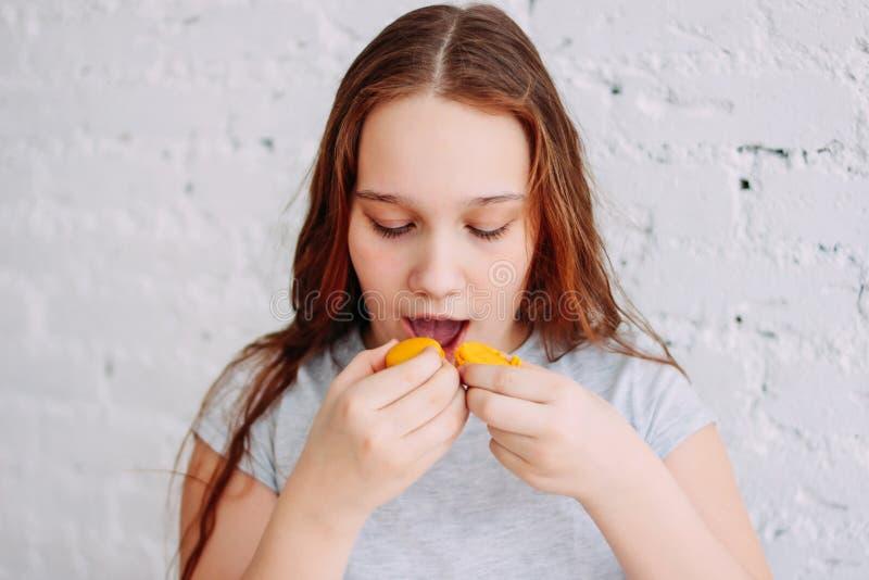 Het tienermeisje heeft twee makarons in een keer, het concept kinderjarenzwaarlijvigheid en het te veel eten royalty-vrije stock foto's