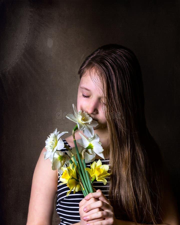Het tienermeisje inhaleert aroma van boeket van gele narcissen stock afbeeldingen