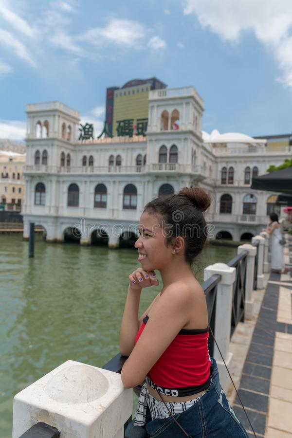 Het tienermeisje kijkt de linker, waterkant van Macao, China, oceaan en blauwe hemel in openlucht weinig wolken royalty-vrije stock foto