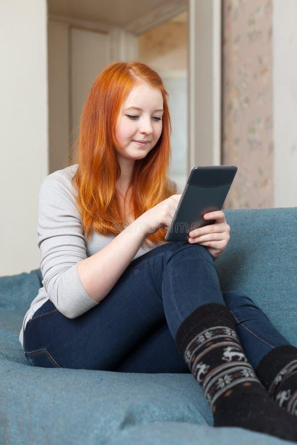 Het tienermeisje leest e-lezer of tabletcomputer royalty-vrije stock afbeelding