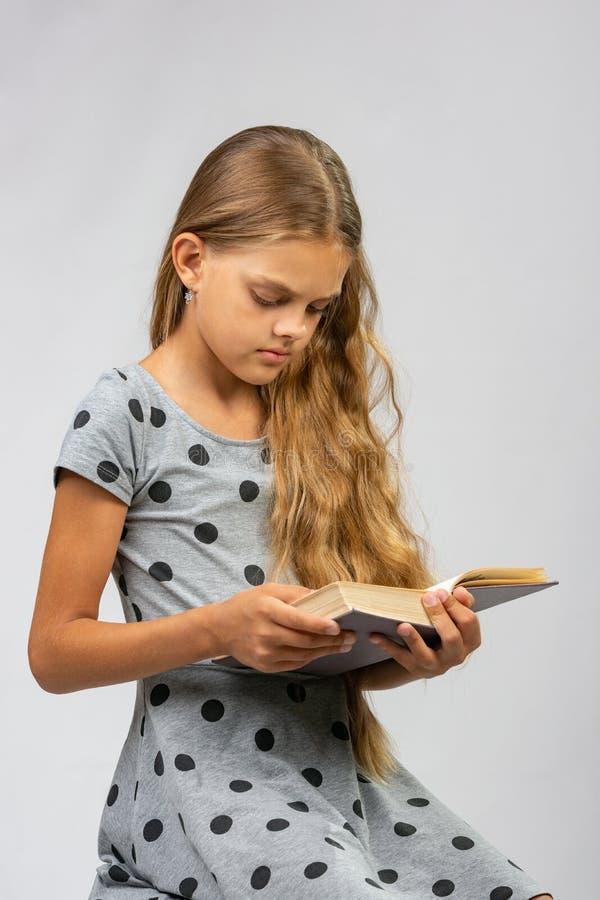 Het tienermeisje leest een boek royalty-vrije stock afbeelding