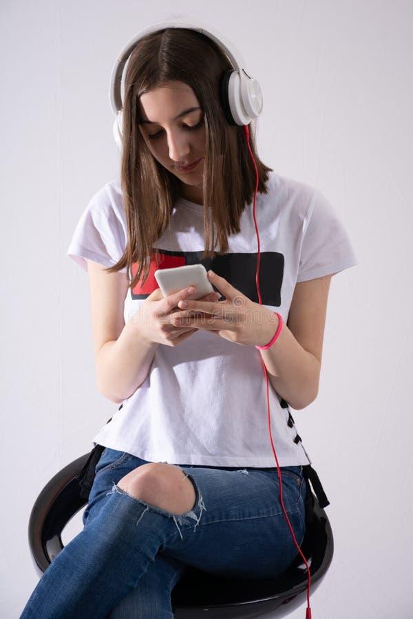 Het tienermeisje luistert aan muziek op hoofdtelefoon en schrijft bericht op celtelefoon op witte achtergrond wordt geïsoleerd di royalty-vrije stock afbeelding